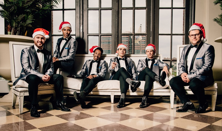 The Doo Wop Project members wearing tuxes and with Santa hats on their heads.
