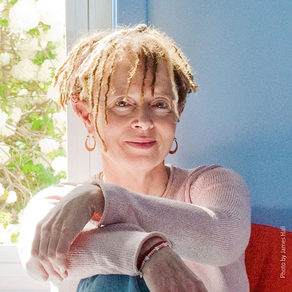 Anne Lamott seated on a chair with her arms crossed over one knee.