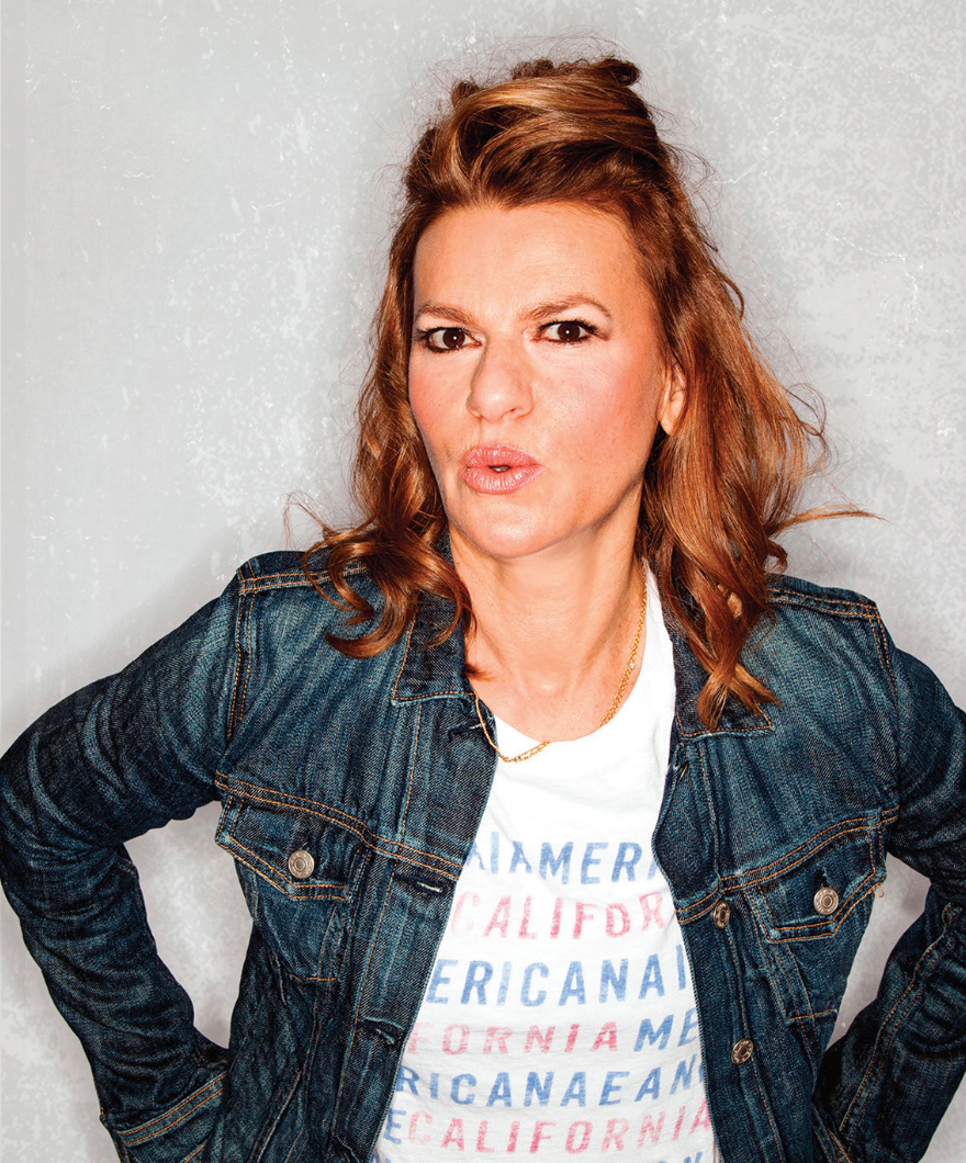 Sandra Bernhard posing in a denim jacket and a shirt that says California