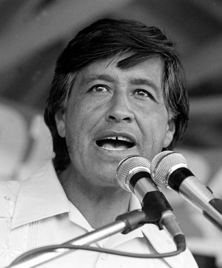 Black and White image of Cesar Chavez speaking behind a microphone